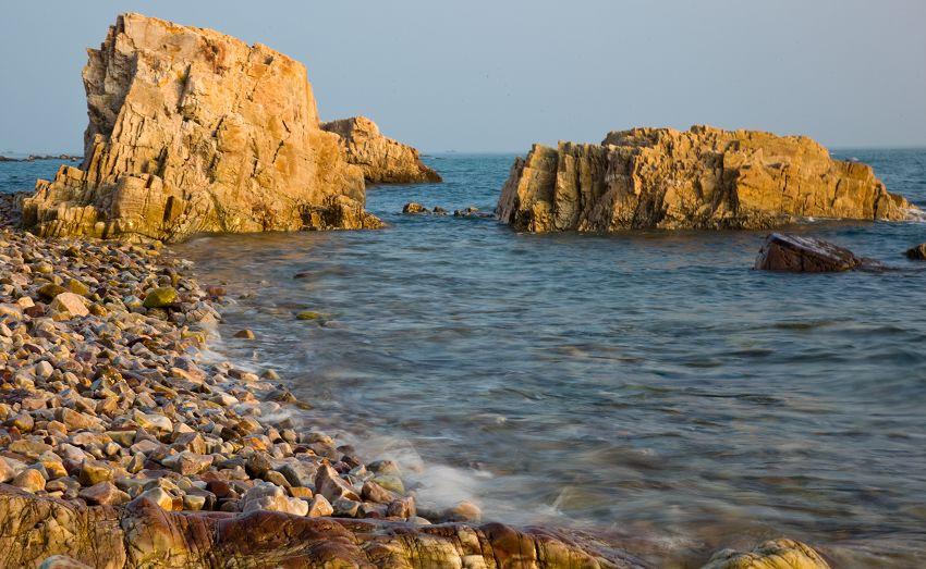 """在辽东半岛与山东半岛之间的渤海海峡上,镶嵌着32颗苍翠如黛的明珠,这就是被世人誉为""""海上仙山""""的美丽群岛——长岛。 长岛,即庙岛群岛,陆地面积56.96平方公里,山水相依,如诗如画,是全国第一个海岛地质公园。独特的地理位置和数亿万年地质变迁史,使这里形成了独具特色的海蚀地貌、火山地貌、海积地貌等地质遗迹,奇礁异石众多,自然形成的地质地理状态不仅具有典型性和稀有性,而且未受到破坏,是一个安静美丽的海上世外桃源。 1--"""