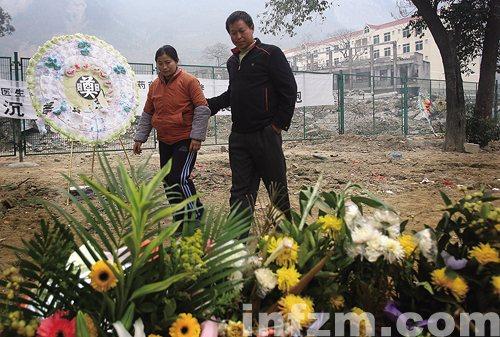 丈夫徐昌军走在北川中学的遗址上,他们在地震中失去了一儿一女.图片