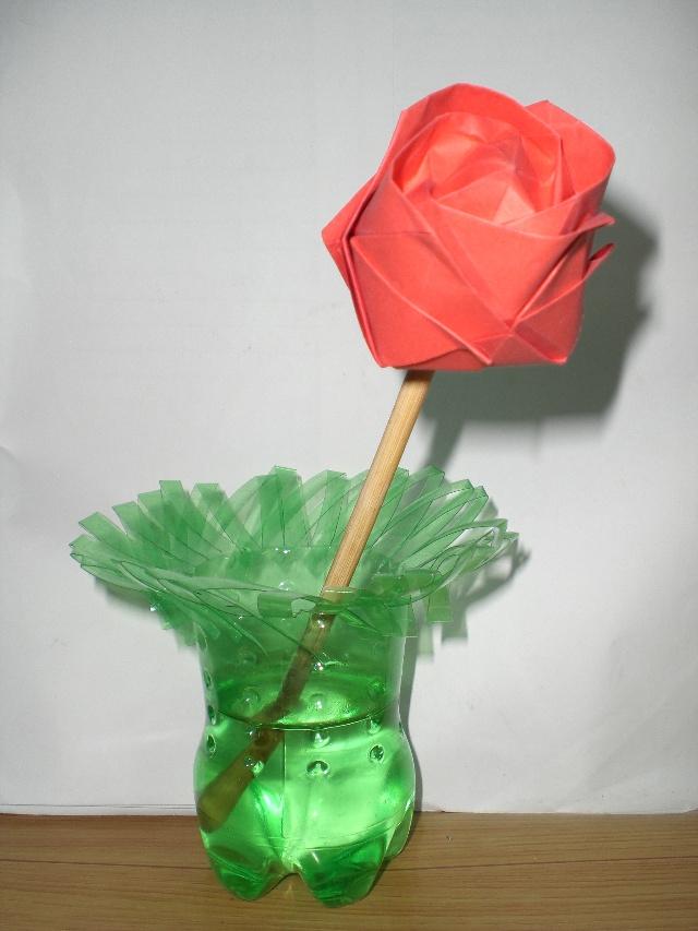 嘿嘿,又跟大家见面了!今天用可乐塑料瓶做了一个美丽的花瓶,附上照片,大家鉴赏一下,看像不?制作过程很简单哦,有时间你也试试!  完成品  插上折纸红玫瑰,效果不错吧  红花需得绿叶配,那就来点绿叶吧  最后我把花瓶放置在电脑旁,养殖起吊蓝了,每天上网的同时,瞅几眼绿色,对保护眼睛有好处吧,嘿嘿。。。